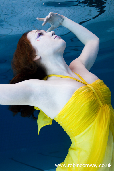 under water model wearing yellow dress